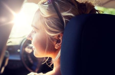 happy teenage girl or young woman in car Standard-Bild
