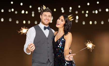 happy couple with crowns and sparklers at party Stock Photo