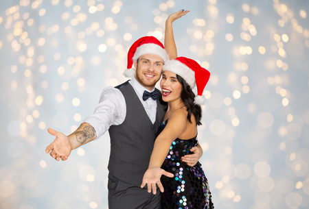 glückliches Paar in den Weihnachtsmützen an der Weihnachtsfeier