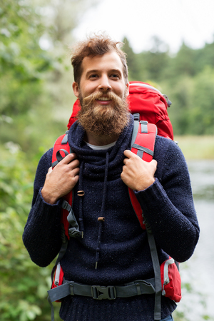 bearded traveler with backpack in woods