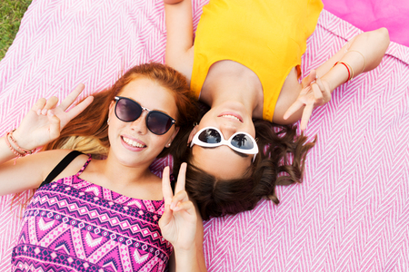 teenage girls in sunglasses showing peace sign
