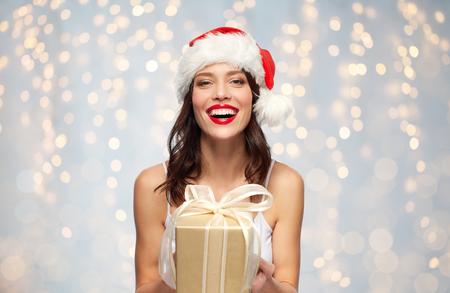 Vrouw in kerstmuts met kerstcadeau Stockfoto - 108525249