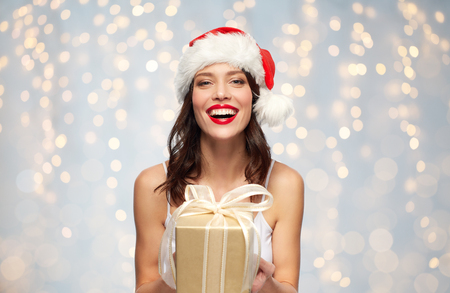 woman in santa hat with christmas gift Banco de Imagens