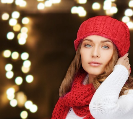 woman in hat and scarf over lights background Archivio Fotografico - 108525767