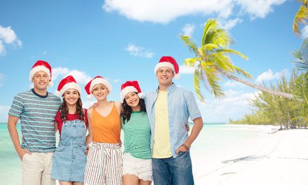 friends in santa hats over beach on christmas Stock Photo