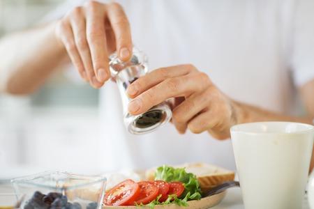 Nahaufnahme der Hände, die Lebensmittel durch Pfeffermühle würzen Standard-Bild