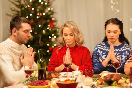 Freunde beten vor dem Weihnachtsessen zu Hause