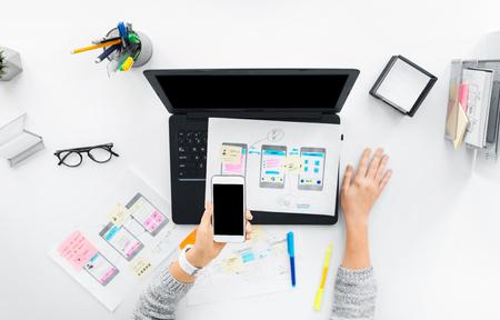 diseñador web con smartphone y portátil en la oficina