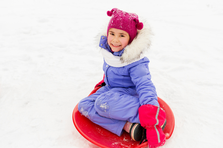 happy little girl with snow saucer sled in winter Stock fotó