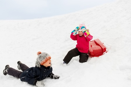happy little kids with sled down hill in winter Stock Photo