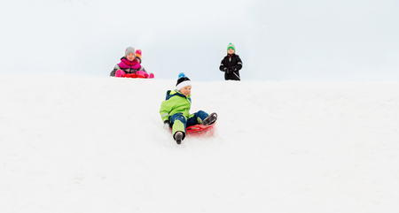 kids sliding on sleds down snow hill in winter Stock fotó