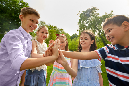 group of happy kids making high five outdoors Stock Photo