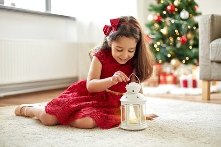 little girl with lantern at home on christmas