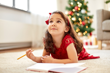 little girl making christmas wish list at home Stock Photo