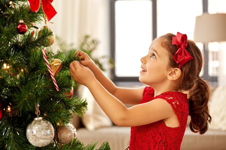little girl decorating christmas tree at home