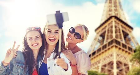 group of smiling women taking selfie in paris