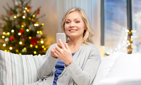 woman with smartphone at home on christmas