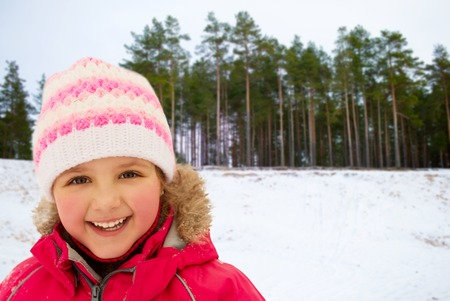happy little girl in winter clothes outdoors