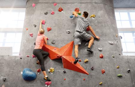 man and woman climbing a wall at indoor gym