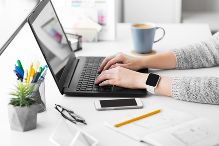 designer with smart watch and laptop at office Stock Photo