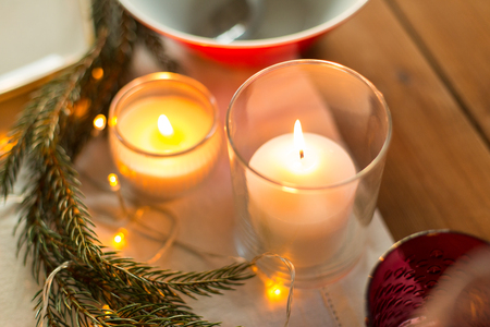 christmas, holidays and decoration concept - burning candles and fir branch on table served for festive dinner at home