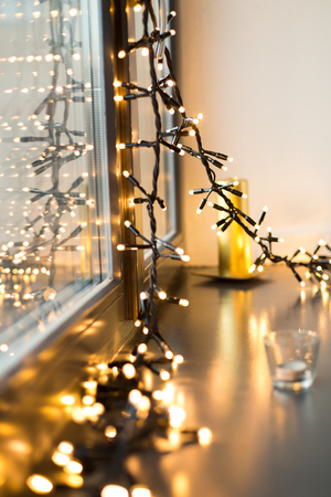 holidays and decoration concept - close up of christmas garland glowing on window sill