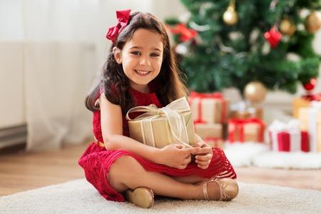 glückliches Mädchen mit Weihnachtsgeschenk zu Hause Standard-Bild