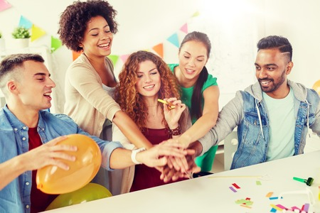 happy business team at office party holding hands