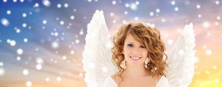 teenage girl with angel wings over snow