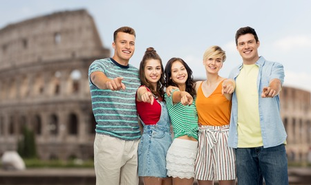happy friends pointing at you over coliseum Stock Photo