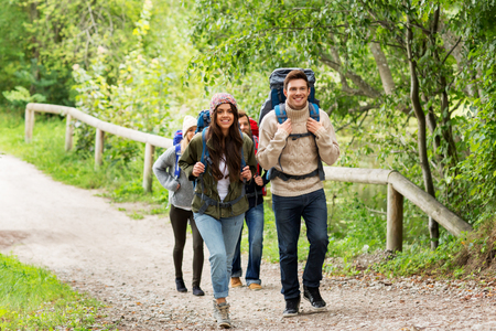 happy friends or travelers hiking with backpacks