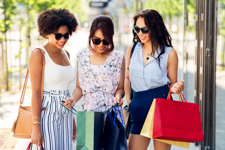 happy women showing shopping bags in city