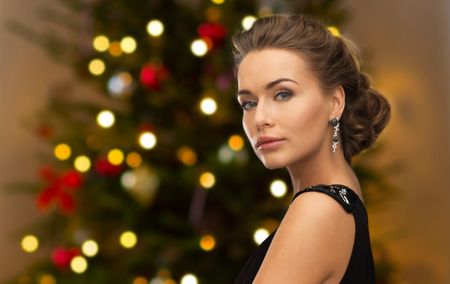people, luxury, jewelry and fashion concept - beautiful woman in black wearing diamond earring over christmas tree lights background