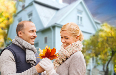 love, relationships and real estate concept - smiling couple with autumn maple leaves over living house background Reklamní fotografie