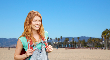 adventure, travel, tourism, hike and people concept - smiling young woman with backpack over venice beach background in california Stock Photo