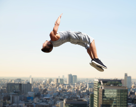 extreme sport, parkour and people concept - young man jumping high over tokyo city background Stock Photo