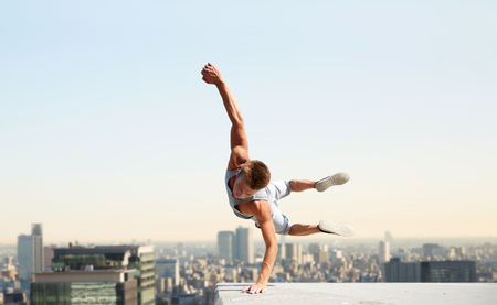 extreme sport, parkour and people concept - young man jumping high over tokyo city background Stockfoto