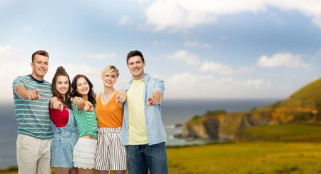 travel, tourism and summer holidays concept - group of happy smiling friends hugging pointing at you over big sur coast of california background