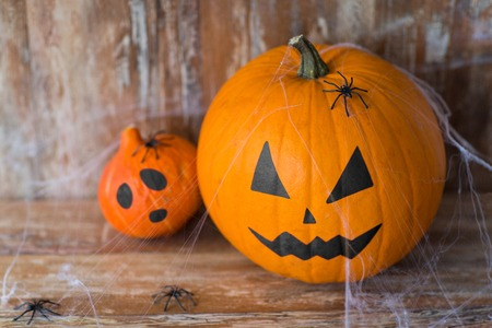 halloween and holidays concept - pumpkin and squash with scary faces, spiders and cobweb