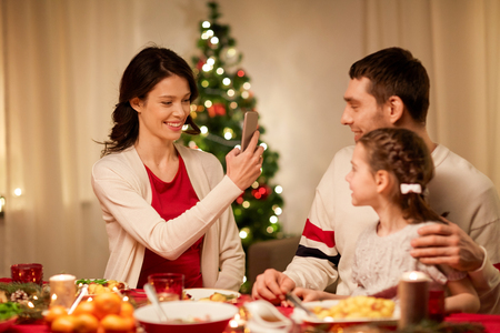 holidays, family and celebration concept - happy mother, father and little daughter having christmas dinner and taking picture by smartphone at home