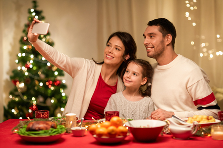holidays, family and celebration concept - happy mother, father and little daughter having christmas dinner and taking selfie picture by smartphone at home Stock Photo