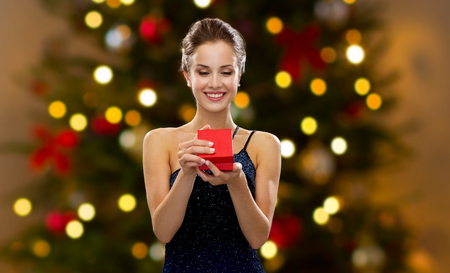 woman with red gift box over christmas tree lights