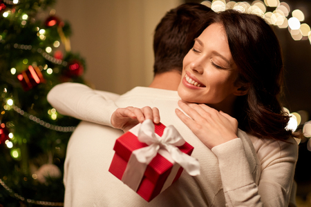 happy couple with christmas gift hugging at home Foto de archivo