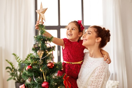 mother and daughter decorating christmas tree Stockfoto