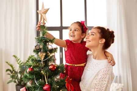 Mutter und Tochter schmücken Weihnachtsbaum