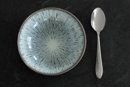 table setting and eating concept - ceramic plate and spoon served for dinner