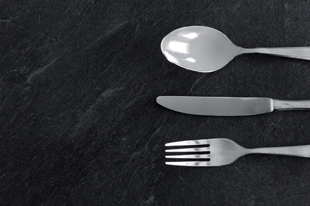 table setting, cutlery and eating concept - close up of fork, knife and spoon
