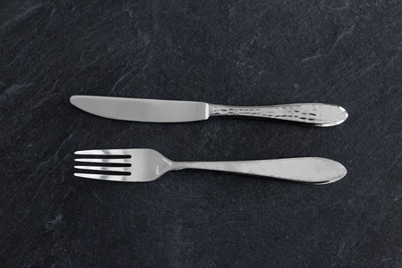 table setting, cutlery and eating concept - close up of fork and knife