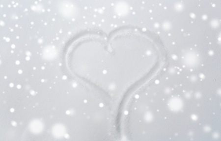 winter holidays, valentines day, love and christmas concept - heart shape silhouette or print on snow surface