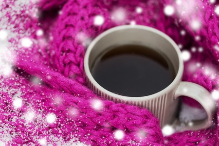 season, drinks, christmas and winter holidays concept - close up of tea or coffee mug and knitted woolen scarf in snow 写真素材